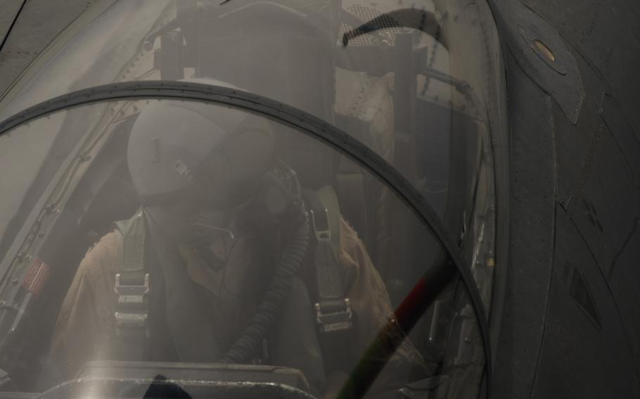 An F-15 combat systems officer looks over at the boom, a long arm that connects the fighter with a KC-135 Stratotanker during a midair refueling operation on March 24, 2016.