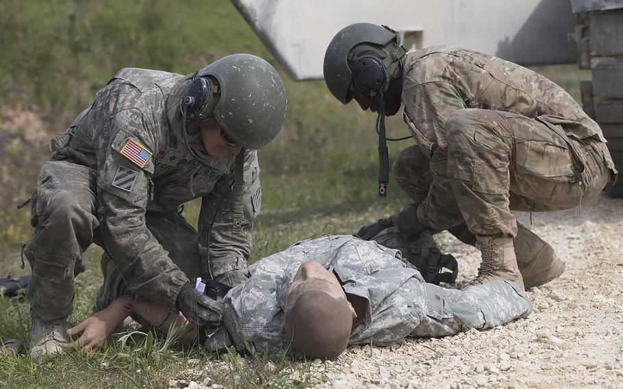 U.S. Army Spc. Stephen Holtzclaw (left) and Sgt. Lionel Ray tend to a simulated casualty during a drill held as part of the 2016 Strong Europe Tank Challenge on Wednesday, May 11, 2016, at the Grafenwoehr, Germany training area.
