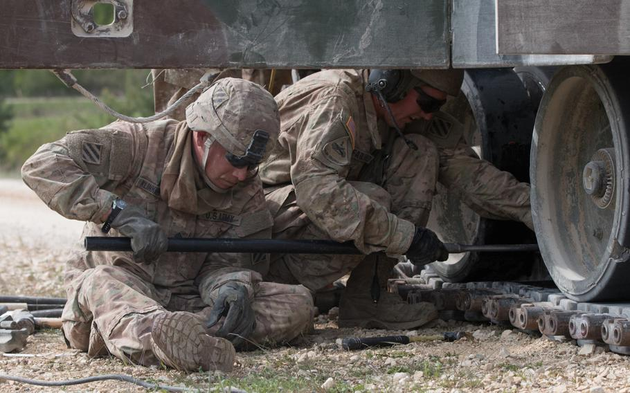 U.S. Army Staff Sgt. Brian Klinkiewicz (left) and Sgt. 1st Class Phillip McFarland put the finishing touches on their ?disabled? M1A2 Abrams battle tank during an improvised explosive device drill at the 2016 Strong Europe Tank Challenge. The soldiers were part of the American force that took part in the six-nation competition held at the Grafenwoehr, Germany training area.