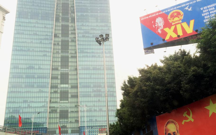 The Lotte building and its department store tower over billboard photos of Ho Chi Minh and communist symbols in Hanoi, Vietnam's capital.