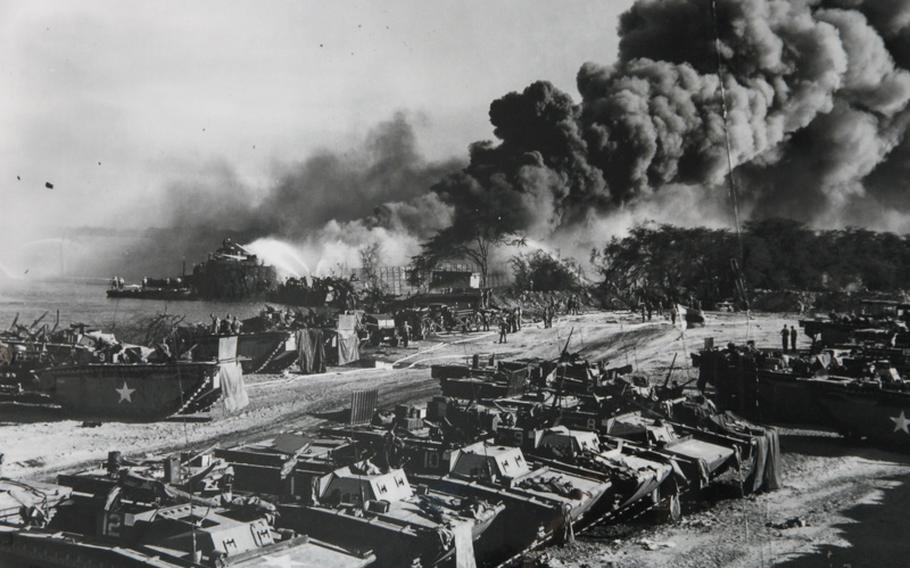 Smoke billows from ships at Pearl Harbor?s West Loch during the disaster of May 1944. The ships had been in the process of being loaded with the tanks in the foreground, which would be used for the retaking of the Mariana Islands during World War II.