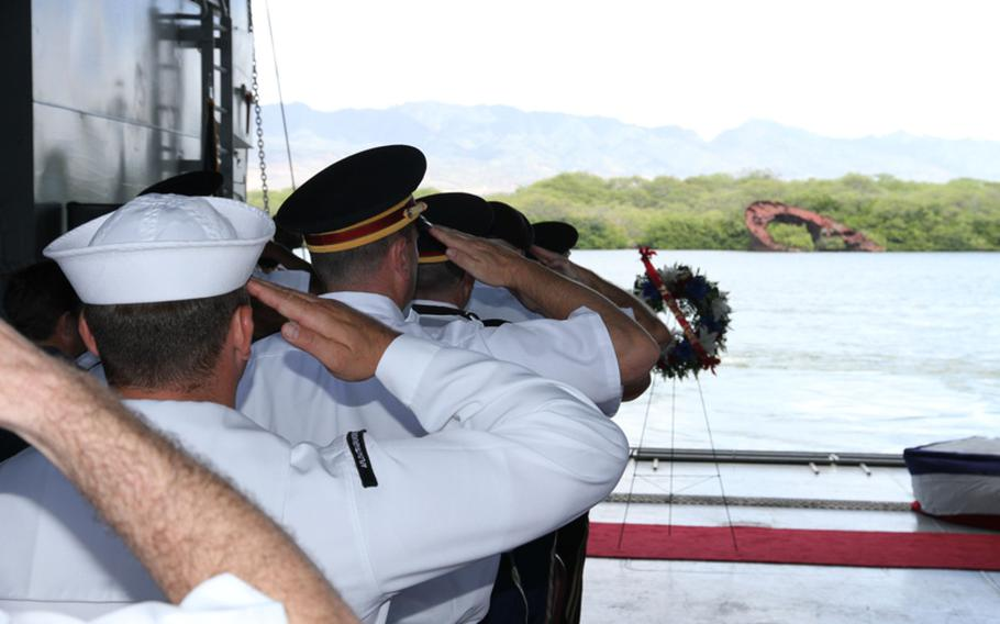 Servicemembers salute during the National Anthem at a memorial aboard the LTG William B. Bunker in Pearl Harbor, May 20, 2016, that commemorated the West Loch disaster of 1944. In the background is the hull of LST 480, one of six Landing Ship, Tank-class vessels that sank as the result of a chain-reaction explosion that killed scores of men.