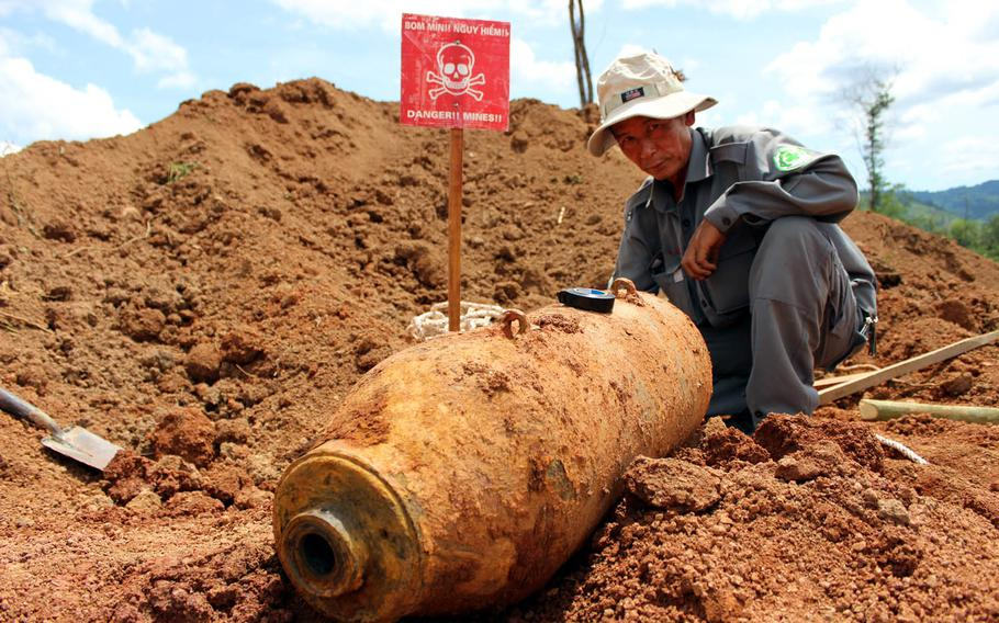 National technical officer Bui Trong Hong, working with Project RENEW, investigates the condition of a 250-pound U.S. aerial bomb found last June five feet underground at a construction site in Quang Tri Province, Vietnam.