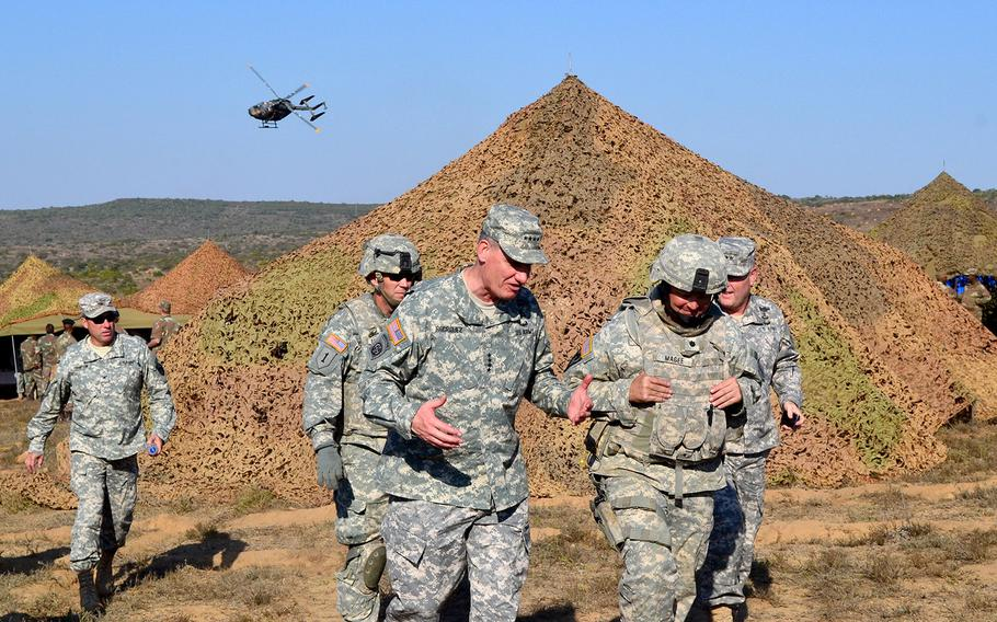 """U.S. Army Gen. David Rodriguez, center, commanding general of U.S. Africa Command, speaks with Lt. Col. Robert E. Lee Magee, commander of 1st Battalion, 18th Infantry Regiment, 2nd """"Dagger"""" Armored Brigade Combat Team, 1st Infantry Division, while visiting the battalion's area of operations on Aug. 2, 2013."""