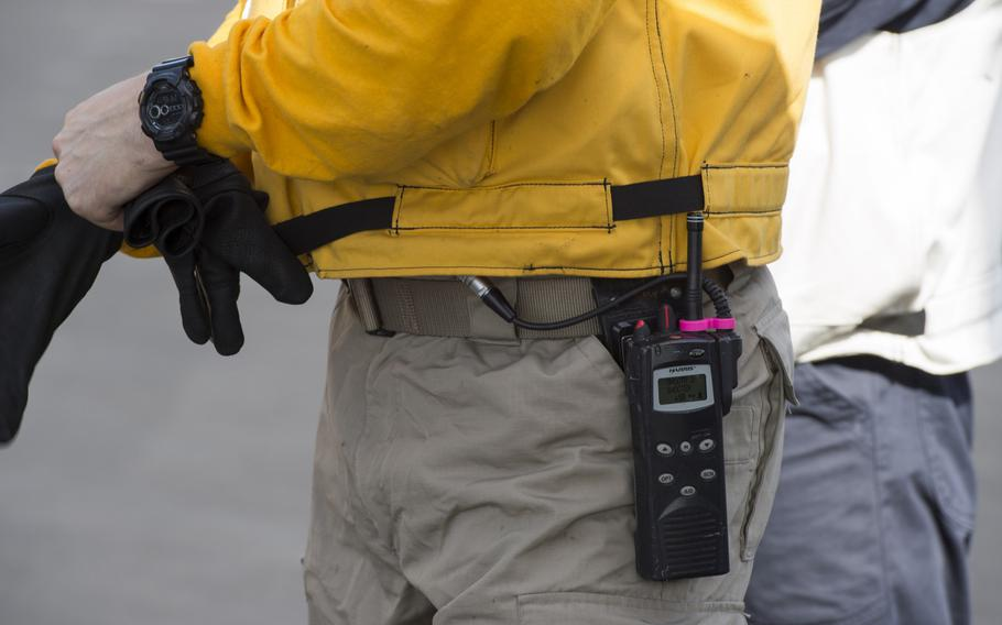 A member of the flight deck crew for the aircraft carrier USS Harry S. Truman has a pink ''Tru Clip'' on his handheld radio to ensure the clasp attachment doesn't crack or break.