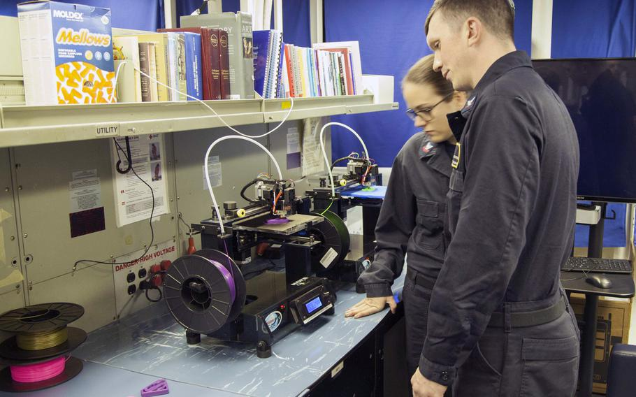 Petty Officer 3rd Class Tyler Stevens, and Petty Officer 2nd Class Ashley Figert, 3D printer technicians onboard the USS Harry S. Truman, watch the printer at work.  The 3D printer shop aboard the Truman invented ''Tru Clips'' to protect attachments for the ship's handheld radios.