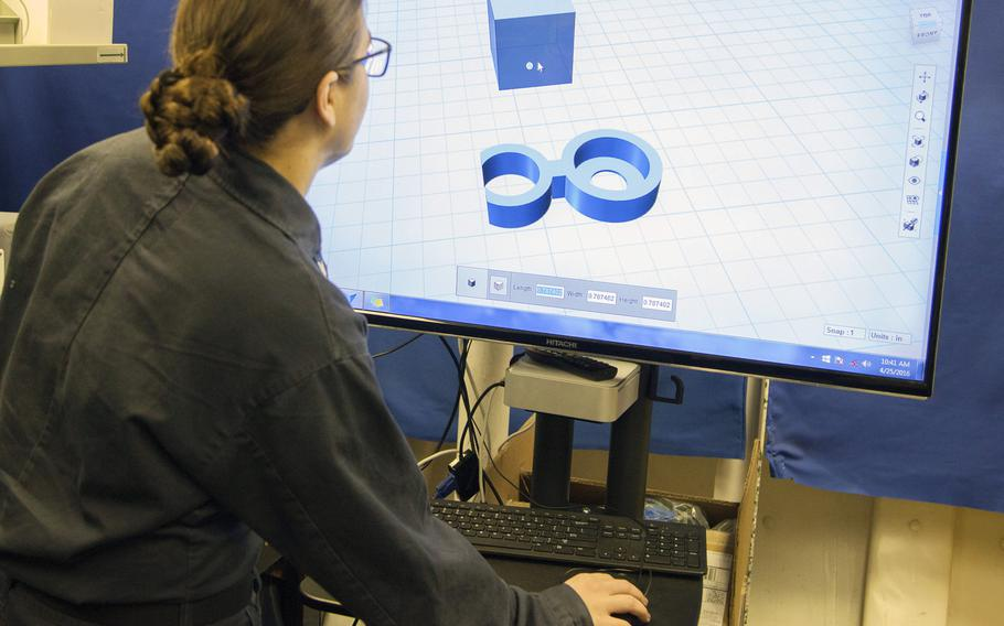 Petty Officer 2nd Class Ashley Figert, a 3D print technician aboard the aircraft carrier USS Harry S. Truman, shows how to create products with the computer-aided design program.  The ''Tru Clip'' design being shown here is being shared with the International Space Station, where it will be used by astronauts.