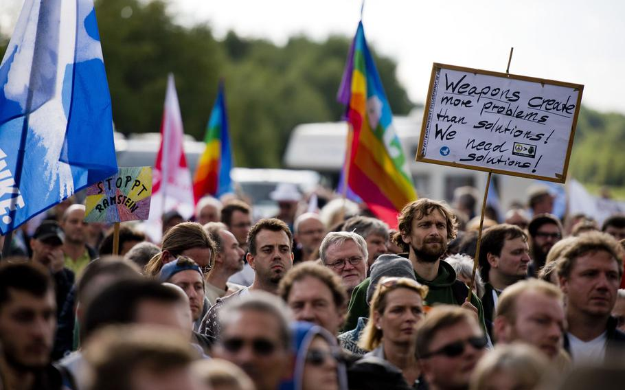 Protesters listen to a speaker during a demonstration outside Ramstein Air Base, Germany, Sept. 26, 2015. Several hundred people gathered to protest military activities at the base. Thousands of peace activists from across Germany and abroad are expected to demonstrate again outside Ramstein Saturday against the base's alleged role in U.S. drone operations.