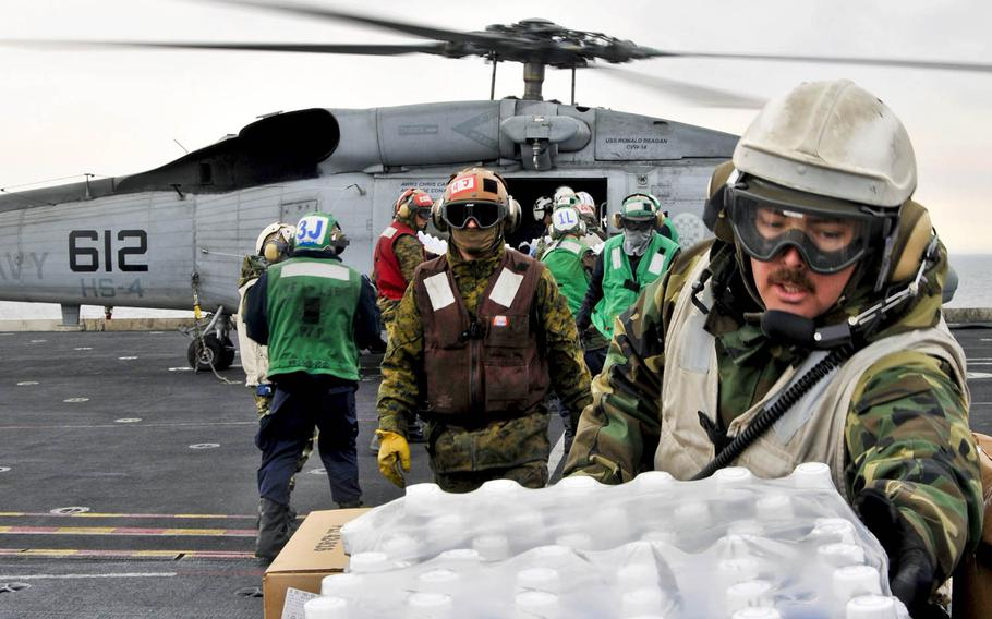 Sailors and Marines aboard the aircraft carrier USS Ronald Reagan load humanitarian supplies onto a Seahawk helicopter in the Pacific Ocean, March 19, 2011. The Ronald Reagan was operating off the coast of Japan in support of Operation Tomodachi.