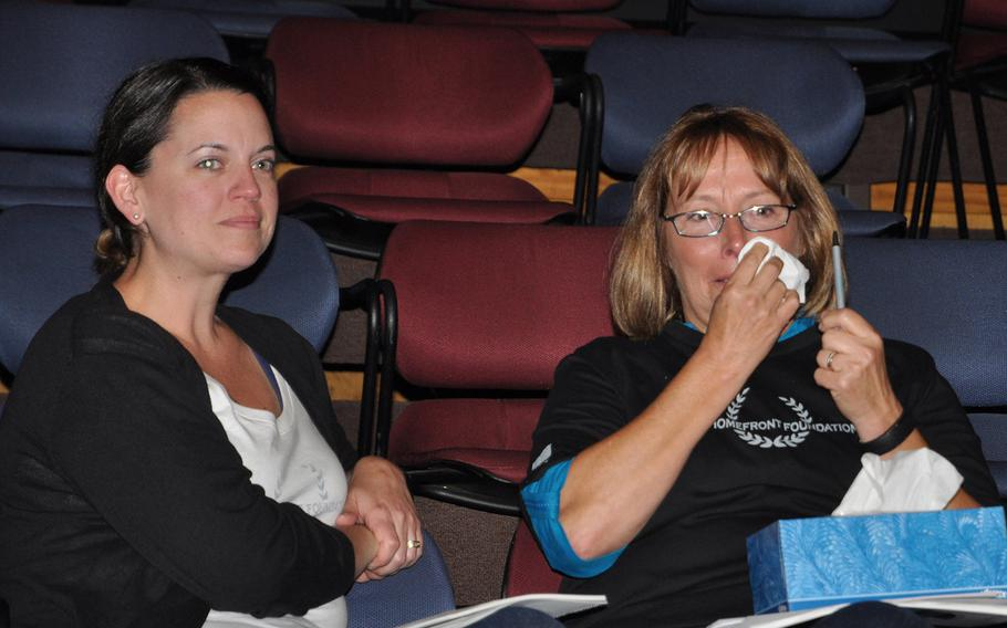 Meghan Zbikowski of the Ariel Group, left, and Tampa Fire Chief Susan Tamme, share an emotional exchange during a storytelling workshop at the University of South Florida theater in Tampa on Aug. 27 for service members and first responders.