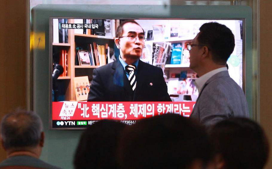 People watch a news program showing a file image of Thae Yong Ho, a minister at the North Korean Embassy in London who defected, at Seoul Railway Station in Seoul, South Korea in August 2016. The high-profile defection is part of a growing trend of people fleeing to the South this year, according to government statistics released Wednesday.