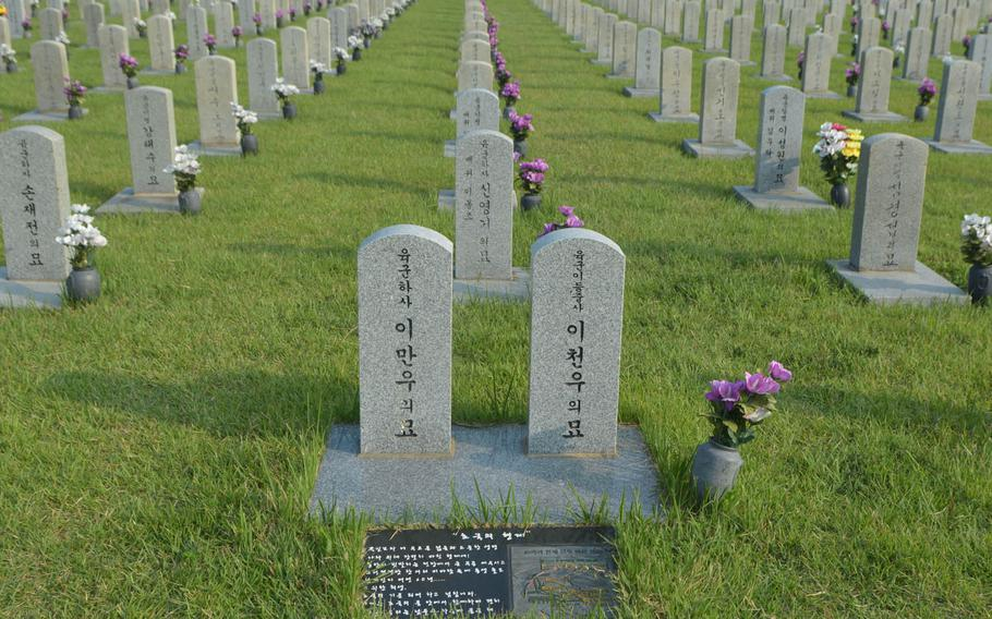 The graves of two South Korean brothers who died while fighting in the Korean War. One was buried in the National Cemetery in Seoul after he died in 1951, while the other was interred in 2010 after his remains were found as part of the military's search efforts.