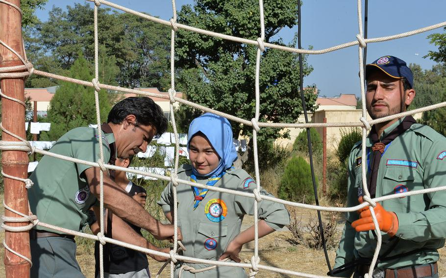 Arifa, a 15-year-old scout from Kabul, who, like many Afghans goes by one name, waits for a scout leader to tie her harness so she can climb a 30-foot rope wall on Sept. 8, 2016, part of a three-day scout event attended by 180 scouts from six troops in the Afghan capital.