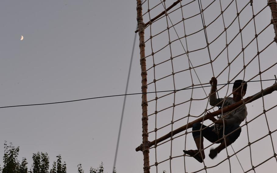 As night falls, Afghan scouts climb a 30-foot wall of rope netting well in Kabul on Sept. 8, 2016, before breaking for dinner. The scouts were participating in a three-day camping event, where they learned outdoor skills, environmental responsibility and tools for building peace.