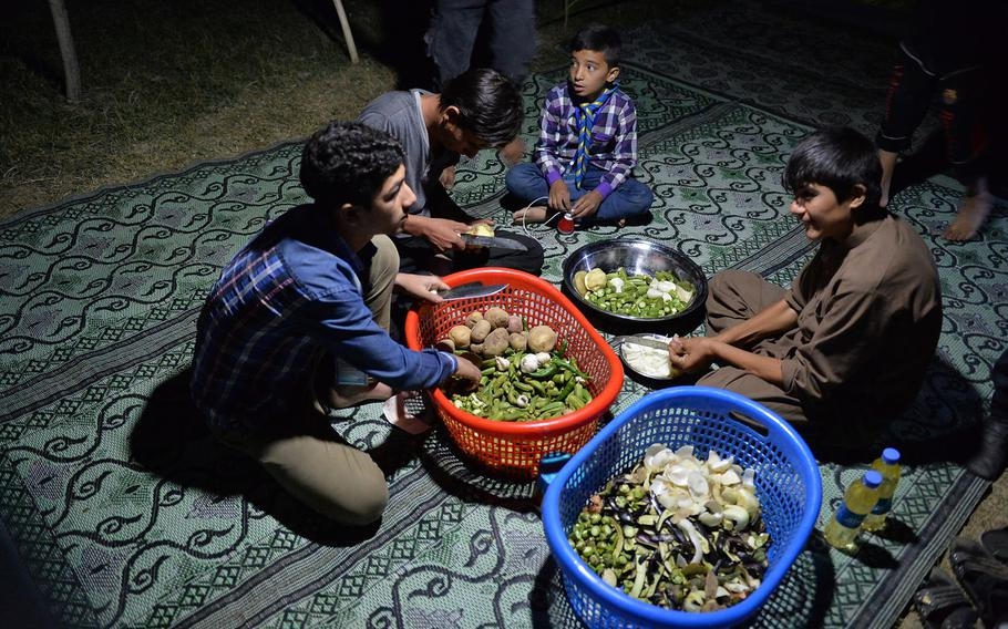Boy scouts slice okra and peel potatoes and onions on Sept. 8, 2016, part of camp duties during a three-day campout in Kabul. The event was a rare opportunity for the children to escape the violence that is a part of daily life in Afghanistan.