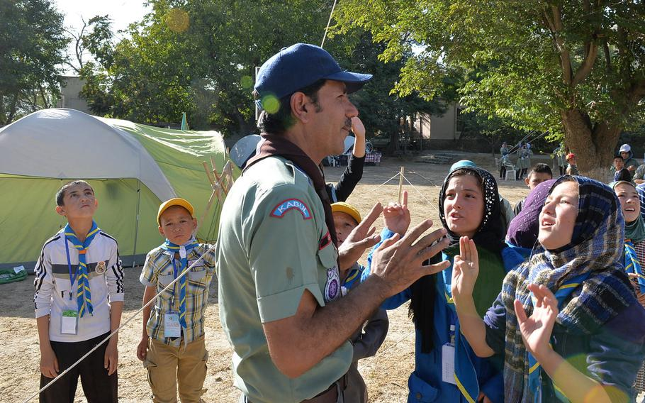 Parsa's Mohsin Arif, a scout trainer and scoutmaster, speaks to Afghan girl scouts begging for a turn to climb a 30-foot rope net climbing wall at a camporee event on Sept. 8, 2016.