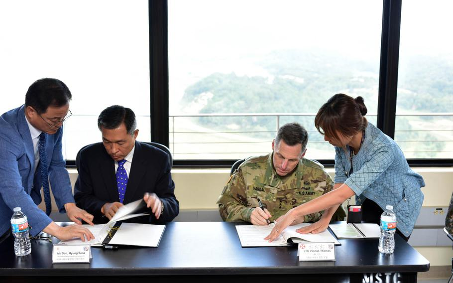 Suh Hyung-suk, an official with South Korea's Ministry of Defense, and Lt. Gen. Thomas Vandal, commander of the 8th Army, sign a memorandum of understanding at the Rodriguez Live Fire Complex near the border with North Korea on Thursday, Sept. 22, 2016.