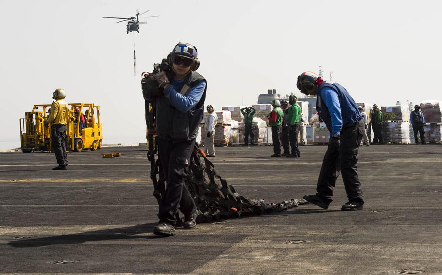 Seaman Skyler Vanoosten, whose rate was Aviation Boatswain's Mate Handling, aboard the aircraft carrier USS Harry S. Truman, carries a net that was used to hold and transport a crate during a replenishment at sea across the flight deck on April 26, 2016.  The Navy has changed the enlisted rating system and no longer has rating titles, instead addressing personnel by their rank.  The Navy also no longer distinguishes between airman, fireman, and seaman.
