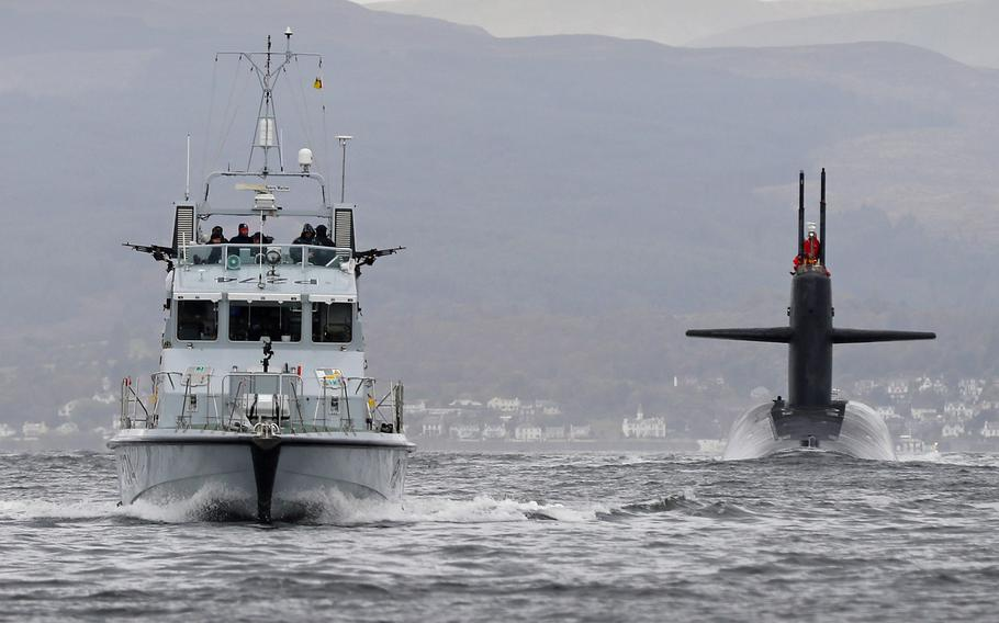 The patrol ship HMS Tracker cruises alongside the submarine USS Tennessee as the sub enters Faslane naval base, Scotland, Friday, Oct. 7, 2016.