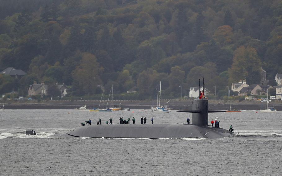 Crewmembers are seen aboard the submarine USS Tennessee as it enters Scotland's Faslane naval base Friday, Oct. 7, 2016.