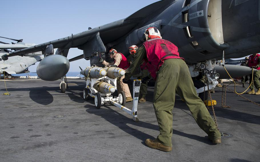 U.S. Marines attach a GBU-54 laser joint direct attack munition bomb to an AV-8B Harrier from the 22nd Marine Expeditionary Unit aboard the amphibious assault ship USS Wasp on Oct. 2, 2016.