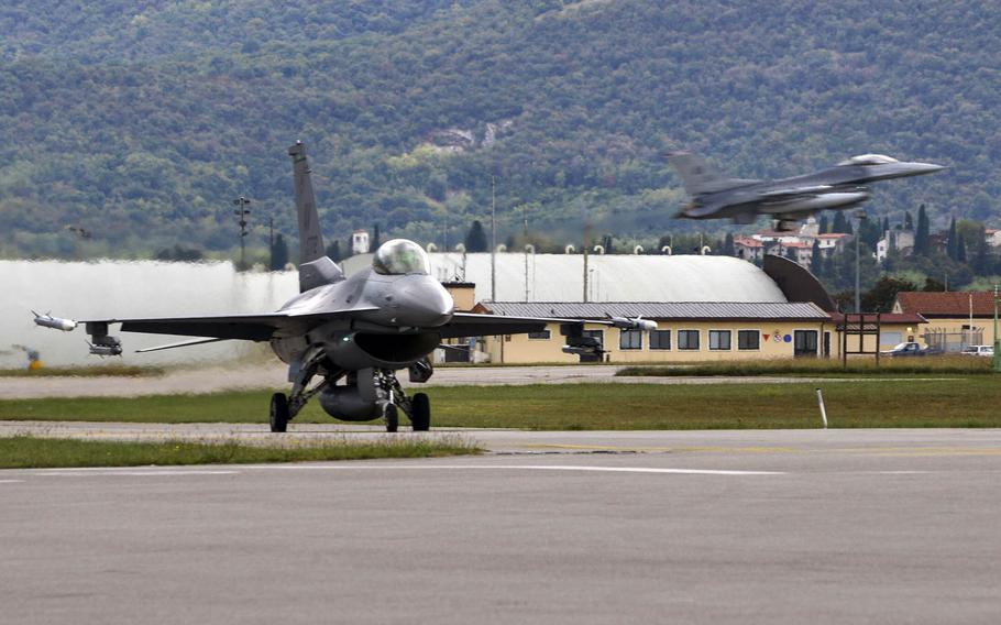 A 555th Fighter Squadron F-16 Fighting Falcon taxis across the runway while a 510th Fighter Squadron F-16 lands at Aviano Air Base, Italy on Oct. 5, 2016. U.S. Air Force F-16s from Aviano have deployed to Djibouti to protect American interests in South Sudan.
