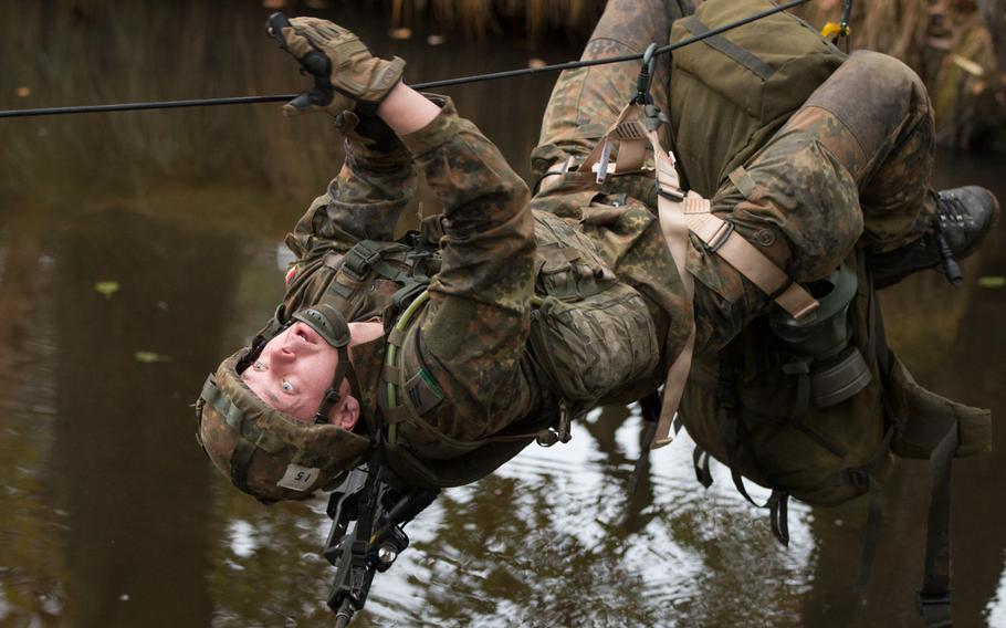 German Pfc. Vitali Krell dangles from a rope as he crosses an ice-cold river during the final day of the 2015 European Best Squad Competition at the Grafenwoehr, Germany, Training Area, Oct. 19-22, 2015. The Germans beat out 16 other squads to earn the title of Best Squad in Europe. German Chancellor Angela Merkel has said Germany must drastically increase its defense spending.