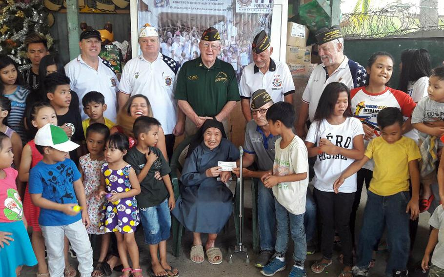 Members of Veterans of Foreign Wars Post 2485 in Angeles City, Philippines, pose with sister Alessandria Casas and orphans at Duyan Ni Maria Children's Home after donating $5,000 to the orphanage near Clark Air Base.