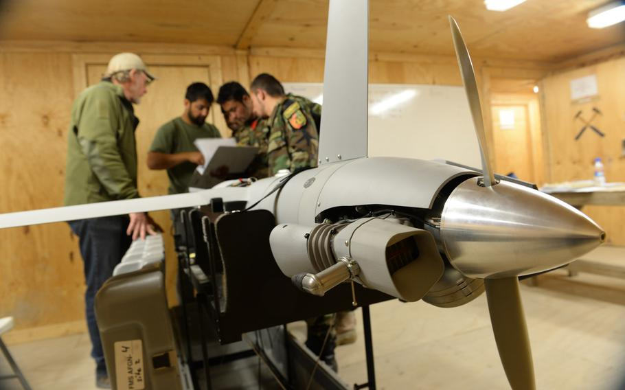 Trainee maintainers check a manual on the ScanEagle unmanned aerial vehicle at a school outside the city of Mazar-e-Sharif on Wednesday, Oct. 26, 2016.