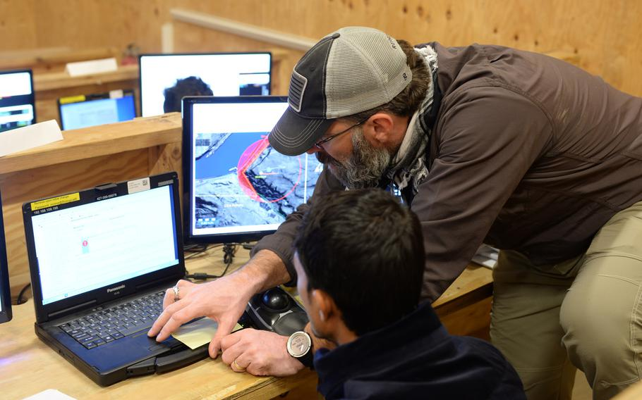 ScanEagle instructor Chris Schoenen helps a student who is training to become a surveillance drone pilots at a school outside the city of Mazar-e-Sharif on Wednesday, Oct. 26, 2016.