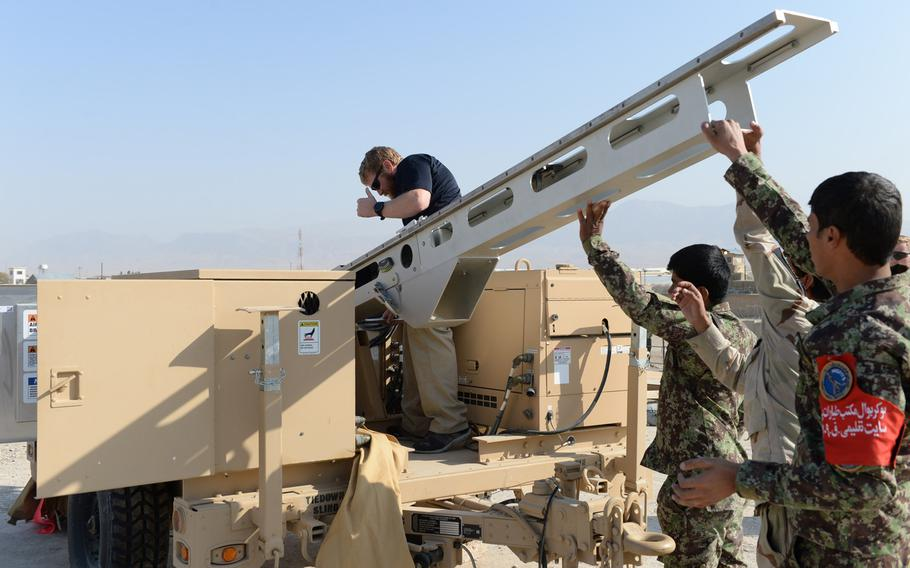 Instructor Cody Cavender helps set up the ScanEagle drone launcher outside a training center near the city of Mazar-e-Sharif on Wednesday, Oct. 26, 2016.