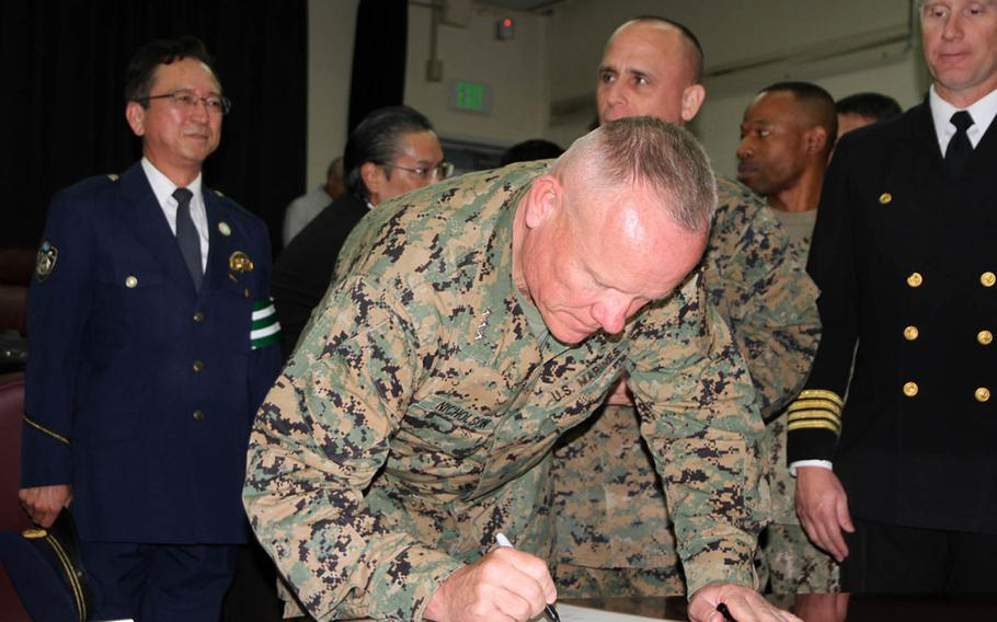 Marine Corps Lt. Gen. Lawrence Nicholson, III Marine Expeditionary Force commander, signs a proclamation Tuesday, Dec. 6, 2016, in Okinawa, Japan. The proclamation launches the Drugged and Drunk Driving Awareness and Prevention Campaign, which will last throughout the holiday season for U.S. forces in Okinawa.