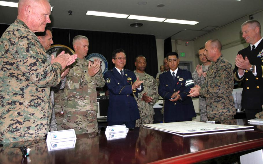 High-ranking officials from each branch of the U.S. military join Japanese police and U.S. embassy officials in applauding the Drugged and Drunk Driving Awareness and Prevention Campaign, Tuesday, Dec. 6, 2016.
