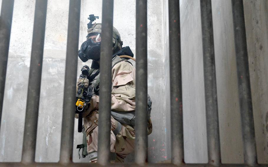 A soldier with the Fort Riley, Kan.-based 3rd Battalion, 66th Armored Regiment, 1st Armored Brigade Combat Team, 1st Infantry Division crouches on a staircase during a drill at Rodriguez Live Fire Range, South Korea, Wednesday, Dec. 7, 2016. The exercise was held with the 501st CBRNE Company as part of training to increase the readiness of troops to confront threat of chemical and biological weapons and nuclear weapons.