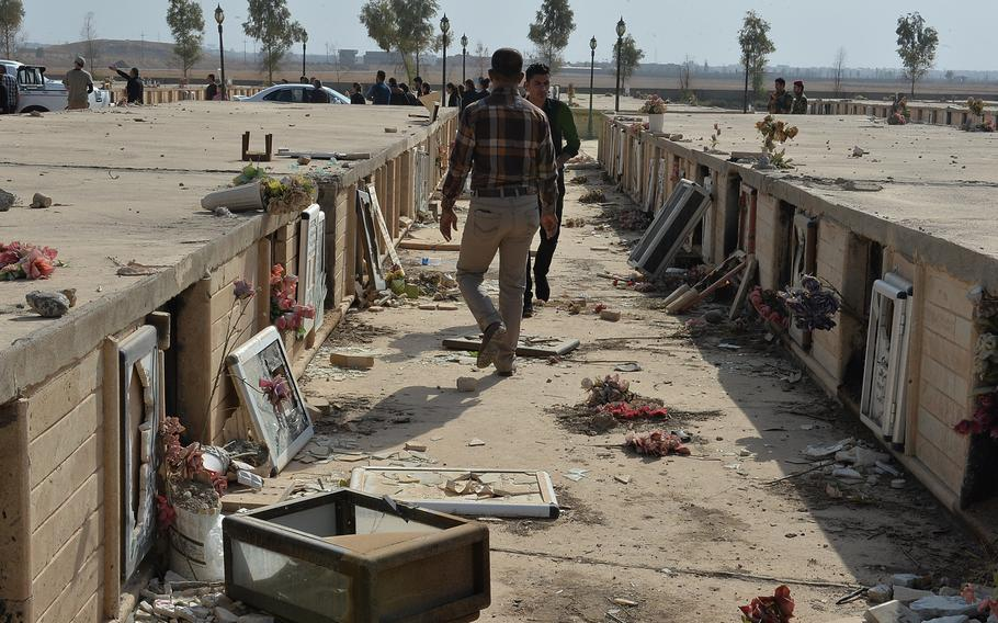 Men walk through the vandalized crypts of Christians at a cemetery on the edge of the recently liberated town of Qaraqosh, Iraq on Nov. 14, 2016. Christian residents fled when Islamic State swept in in 2014 and some returned in October as part of the force to liberate the village.