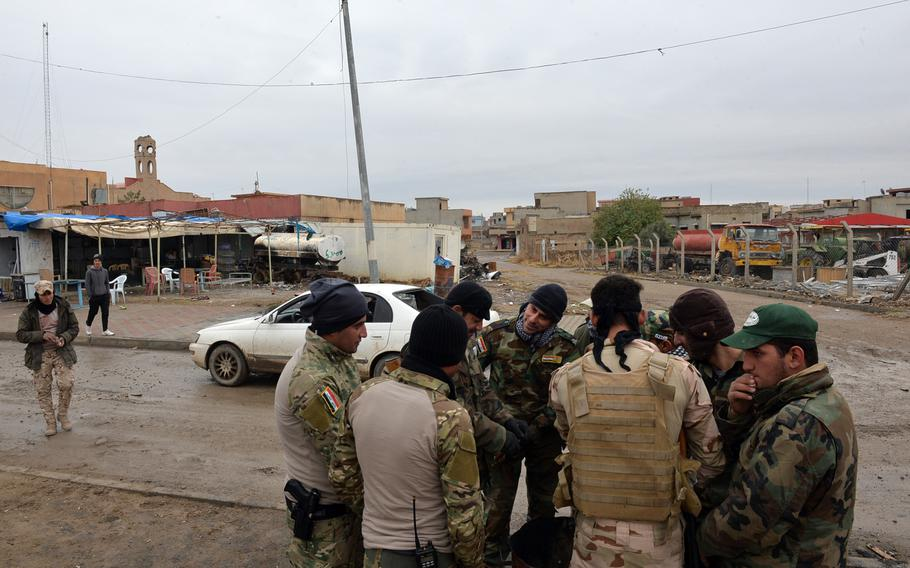Nineveh Plain Protection Units fighters warm their hands at a barrel fire near a command post for the Christian militia in Qaraqosh, Iraq, on Saturday, Dec.17, 2016.