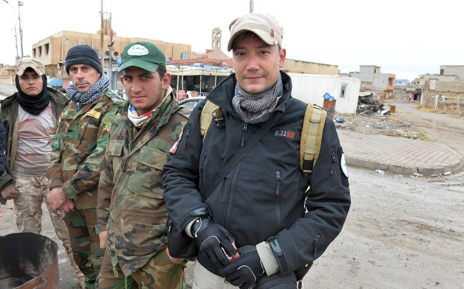 Benoit Kanabus, seen here with members of the Nineveh Plain Protection Units in Qaraqosh, Iraq, on Saturday, Dec. 17, 2016, is a Belgian university professor who volunteered to join the Christian militia in September.