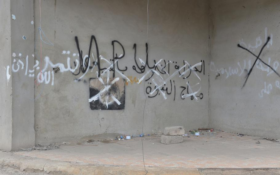 An Islamic State group flag painted on the wall of a building in Qaraqosh, Iraq, on Saturday, Dec. 17, 2016, is painted over with the initials of the Nineveh Plain Protection Units, an Assyrian Christian militia.