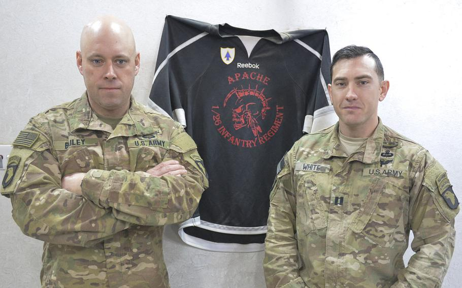 Sgt. 1st Class Brian Bailey, right, and Capt. Jeremy White are pictured on Wednesday, Dec. 28, 2016, with a hockey jersey for Apache Company, 1st Battalion, 26th Infantry Regiment's hockey team at Ft. Campbell, Ky. The jersey decorates a safe house near the forward line of troops in the battle for Mosul, Iraq. Bailey is the company first sergeant and White is the company commander.