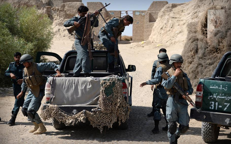 Afghan policemen dismount from a truck during a patrol in Helmand province on Sept. 23, 2014. An Afghan official said Tuesday that an Afghan policeman killed 11 colleagues Monday night before fleeing the scene.