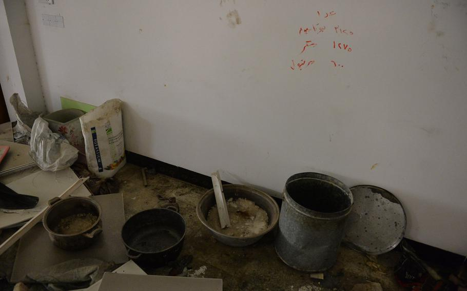 A recipe for rocket propellant is scrawled on the wall of a church building in Qaraqosh, Iraq, behind an array of metal pots and tubs Islamic State munitions makers likely used to mix the formula, Dec. 17, 2016.