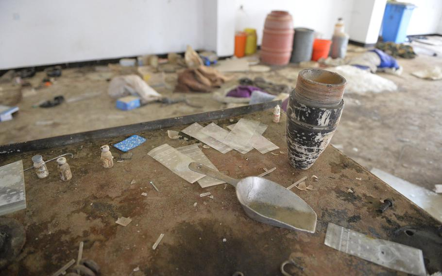 A warhead sits on a table inside a building at St. George's Church in Qaraqosh, Iraq, Dec. 17, 2016. In the background is a station with tubs and barrels filled with chemical precursors for rocket propellant.