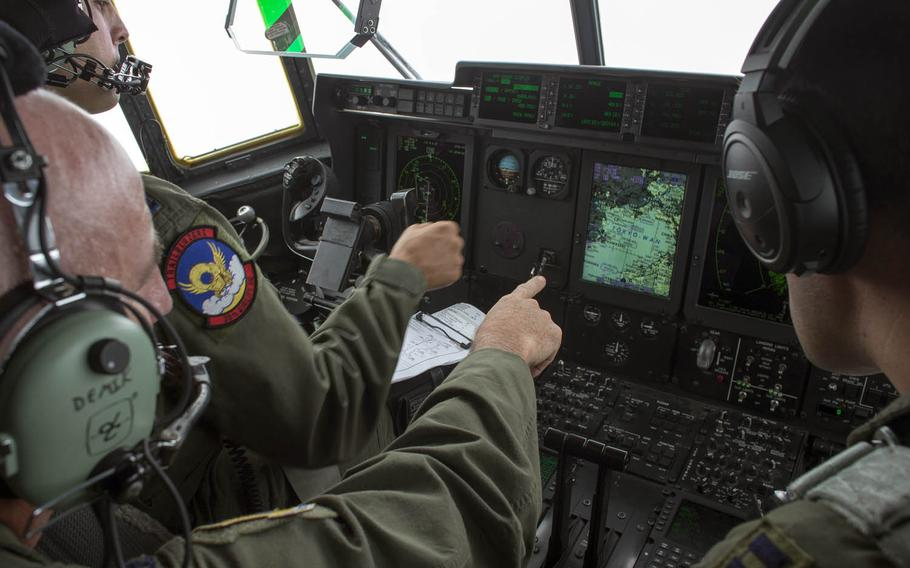Col. Kenneth Moss, center, 374th Airlift Wing commander, checks a map on a C-130J Super Hercules display during a training flight over Tokyo Bay in July.