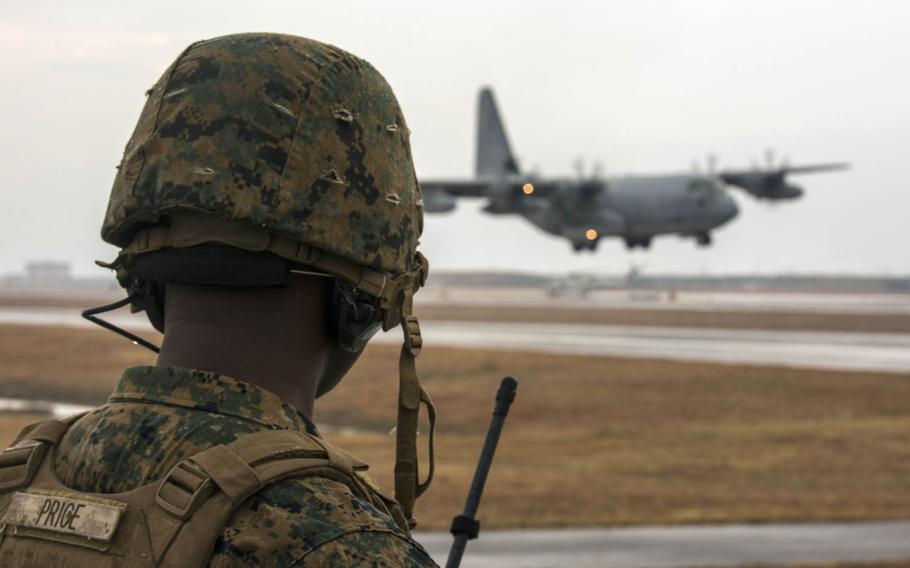 Marine Corps Staff Sgt. George Price directs a KC-130J Hercules during aircraft landing zone training at Marine Corps Air Station Iwakuni, Japan, in late December.