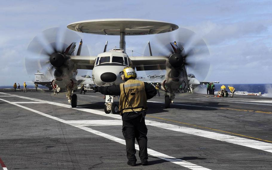 A sailor directs an E-2D Hawkeye assigned to the Tigertails of Airborne Early Warning Squadron 125 across the flight deck of the USS Theodore Roosevelt in 2015.