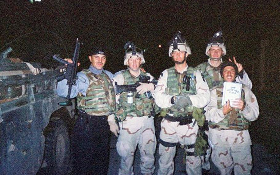 Soldiers with the 101st Airborne Division, including then-Sgt. 1st Class Eric Geressy (second from left) pose with an Iraqi police officer and interpreter in Mosul, Iraq 2003.
