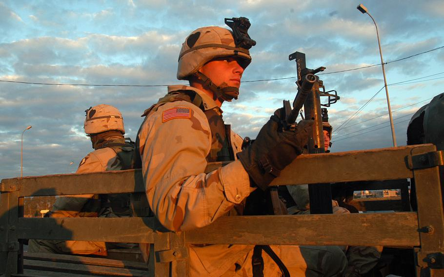 Pfc. Brent Phillips, a mortarman from Hickory Ridge, Ark., sits in the back of a Humvee with an M4 carbine during a morning patrol for roadside bombs in Mosul, Iraq, Nov. 21, 2003.
