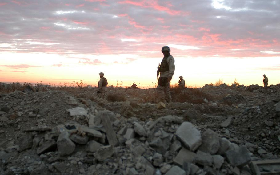Mortar platoon soldiers based at Camp Widowmaker in Mosul, Iraq, search for bombs at sunrise Nov. 21, 2003. The mortarmen were with the Headquarters and Headquarters Company, 3rd Battalion, 2nd Brigade Combat Team, 502nd Infantry Regiment, based in Fort Campbell, Ky.