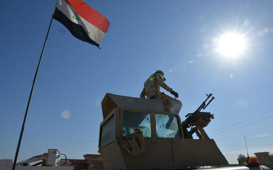 A soldier from Iraq's 9th Armored Division sits atop the turret of his Humvee near Mosul on Nov. 19, 2016.