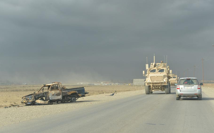 A convoy of Mine Resistant Ambush Protected vehicles passes a burned-out truck on a road near Qayara, Iraq, on Nov. 10, 2016.